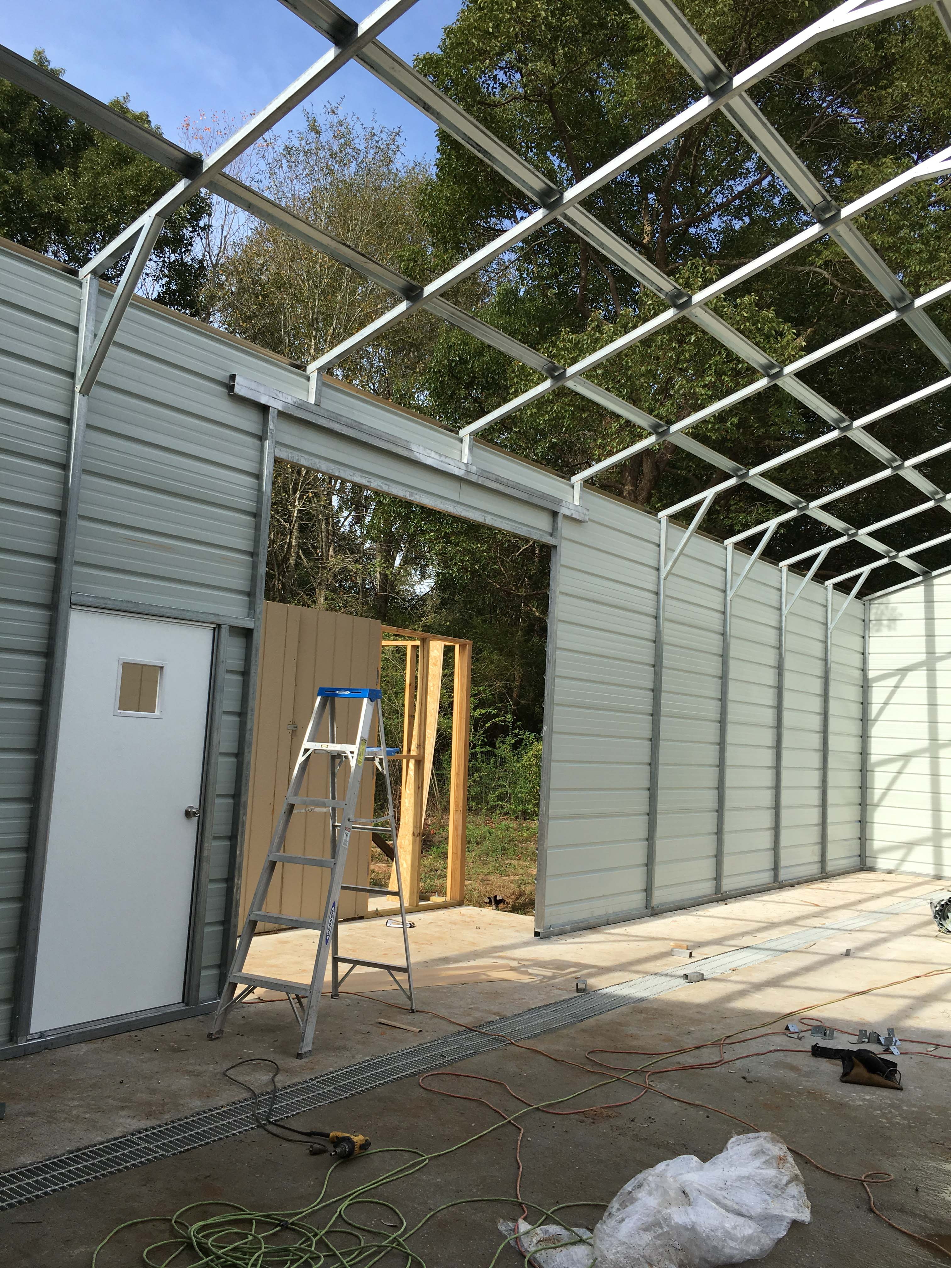 look inside a steel garage job gatorback carports here s the side wall of this job before we installed the roof and roll up door we ve still got work to do but the side wall is getting finished and the